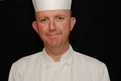 Smiling chef portrait. Portrait of a smiling chef on black background Stock Photography