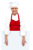 A smiling chef posing behind white billboard Stock Photography