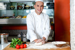 Smiling chef preparing pizza base Royalty Free Stock Photos