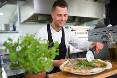 Smiling chef preparing pizza in kitchen Stock Photos