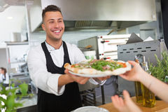 Smiling chef preparing pizza in kitchen Stock Image