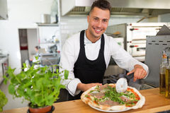 Smiling chef preparing pizza in kitchen Stock Photography