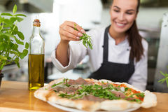 Smiling chef preparing pizza in kitchen Stock Images