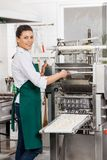 Smiling Chef Processing Ravioli Pasta In Machine Stock Photo