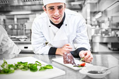 Smiling chef putting mint with his dessert. In the kitchen Royalty Free Stock Photo