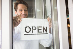 Smiling chef putting up a sign on window Royalty Free Stock Photography