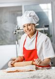 Smiling Chef Rolling Pasta Sheet At Counter Royalty Free Stock Photos