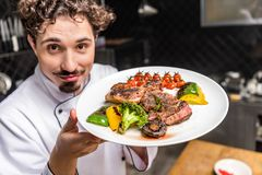 smiling chef showing cooked vegetables with meat royalty free stock photos