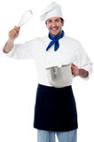 Smiling chef showing kitchen essentials Stock Images