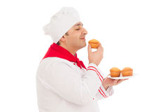 Smiling Chef smelling tasty muffin wearing red and uniform. Over white background Royalty Free Stock Photos
