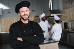 smiling chef standing with crossed arms and looking at camera royalty free stock photo