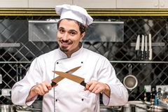 Smiling chef standing. With crossed knifes royalty free stock photos