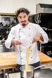 smiling chef standing with pasta on fork and looking royalty free stock photography