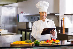 Smiling chef using digital tablet while cutting vegetables Royalty Free Stock Images