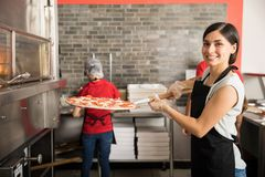 Pretty woman chef putting fresh made pizza in oven. Smiling chef wearing uniform putting raw pizza in modern oven for baking while looking at camera and staff stock images