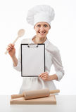 Smiling chef woman cook holding blank clipboard and spoon Royalty Free Stock Images