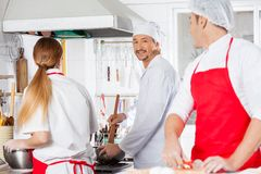 Smiling Chef Working With Colleagues At Kitchen Royalty Free Stock Photo