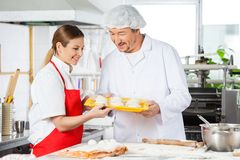 Smiling Chefs Holding Pasta Tray In Kitchen Stock Image