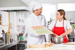 Smiling Chefs Preparing Ravioli Pasta In Kitchen Stock Photos
