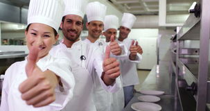 Smiling chefs standing in a row giving thumbs up stock video