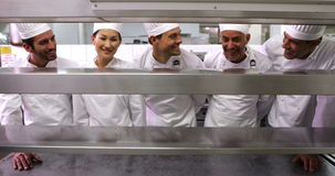Smiling chefs standing in a row at the order station stock footage