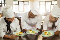Smiling chefs team holding dessert plates Stock Photography