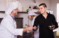 Smiling chefs and waiter working Royalty Free Stock Image
