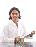 Smiling Chemist. Male In White Lab Coat With Clipboard And Chemicals Royalty Free Stock Images