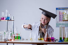 Smiling chemist mixes reagents in flask, close-up Royalty Free Stock Photography