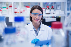 Smiling chemist wearing safety glasses and using tablet pc Stock Photography