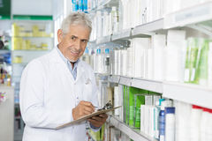 Smiling Chemist Writing On Clipboard While Standing By Shelves Stock Image