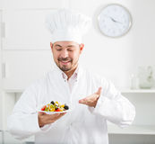 Smiling chief showig greek salad Royalty Free Stock Image