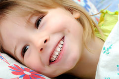 Smiling child. Lying in bed Royalty Free Stock Image