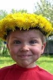 Smiling Child. A smiling child with a wreath of dandelions royalty free stock images
