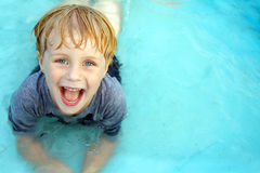 Smiling Child in Baby Pool. A super happy child is laying in a small wading pool, looking up at the camera and smiling.  Empty space off to the side for text / Royalty Free Stock Photography