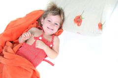Smiling child in bed over white Stock Photography