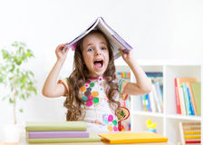 Smiling child with a book over her head in primary Stock Image