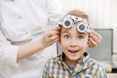 Smiling child boy in glasses checks eye vision pediatric ophthalmologist. Cheerful smiling child boy in glasses checks eye vision pediatric ophthalmologist royalty free stock photo