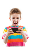 Smiling child boy playing games or surfing internet on smartphon Royalty Free Stock Images