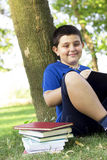 smiling child boy reading book outdoor on green grass field Royalty Free Stock Photo