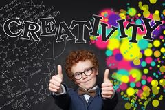 Smiling child boy showing thumb up on background with science formulas  and arts pattern.  royalty free stock images