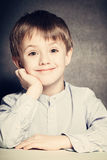 Smiling Child Boy Sits at School Desk Stock Images