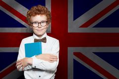 Smiling child boy student on the UK flag background. Learn English concept.  royalty free stock photography
