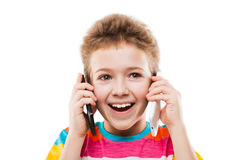 Smiling child boy talking two mobile phones or smartphones. Beauty smiling child boy hand holding two mobile phones or talking pair of smartphones white isolated Royalty Free Stock Image