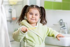 Smiling child brushing teeth Stock Photo