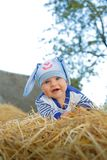 Smiling child in a Bunny suit smiling and posing on the straw royalty free stock images