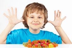 Smiling child with candies on white background Royalty Free Stock Images
