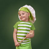 Smiling child chef with a big wooden spoon. On green background Royalty Free Stock Photos