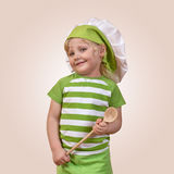 Smiling child chef with a wooden spoon. On a beige background Royalty Free Stock Image