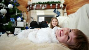 Smiling child close up portrait, happy girl lying on bed, christmas eve, sisters having fun at home